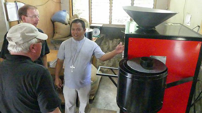 Bischof Dimoc erklärt Missio-Präsident Msgr. Huber und Weihbischof Georgens die Kaffeeröstmaschine. © Ingrid Moos